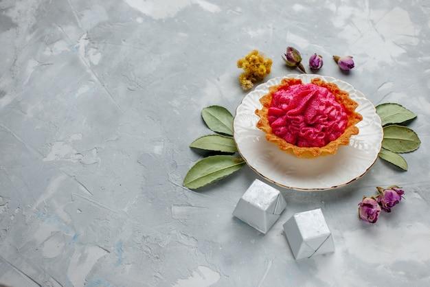 Heerlijke cake met roze room en chocolade op lichtbureau, zoete bakroom van het cakekoekje