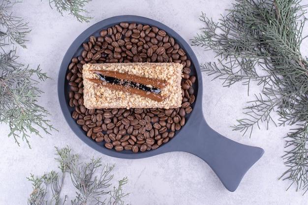 Heerlijke cake op donker bord met koffiebonen. hoge kwaliteit foto