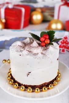 Heerlijke cake op schotel met parels op de achtergrond van de kerstmisdecoratie