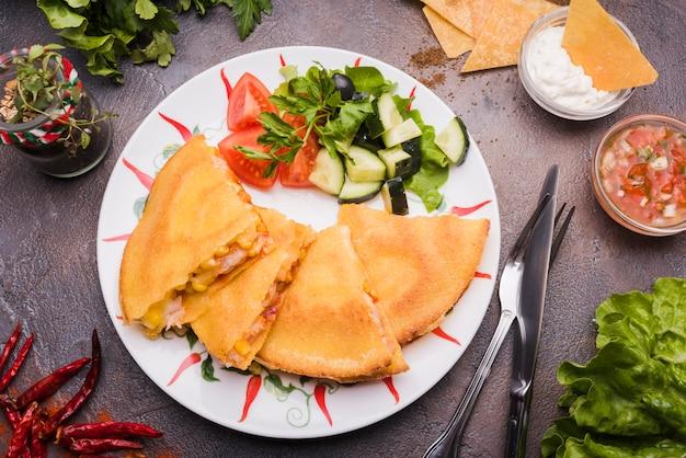 Heerlijke cakes dichtbij plantaardige salade op plaat onder nachos met saus en bestek