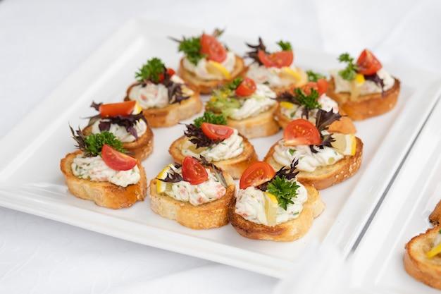 Heerlijke canapé met worst en tomaat.canapes op witte keramische platen op bruiloft receptie.