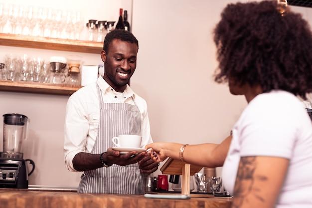 Heerlijke cappuccino. aangename positieve man die een kopje koffie vasthoudt terwijl hij deze voor een klant klaarmaakt