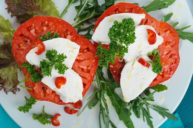 Heerlijke caprese salade met mozzarellakaas, rijpe tomaten en verse ruccola. bovenaanzicht