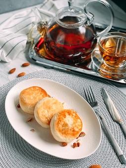 Heerlijke cheesecakes pannenkoeken met theekop en theepot op zilveren dienblad op keukendoek
