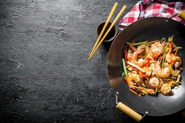 Heerlijke chinese wok udon noedels met verse groenten, saus en garnalen op zwarte rustieke tafel