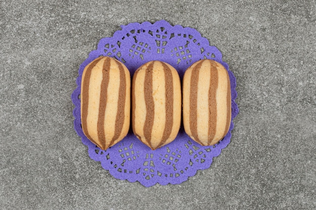 Heerlijke chocolade gestreepte koekjes op blauw servet
