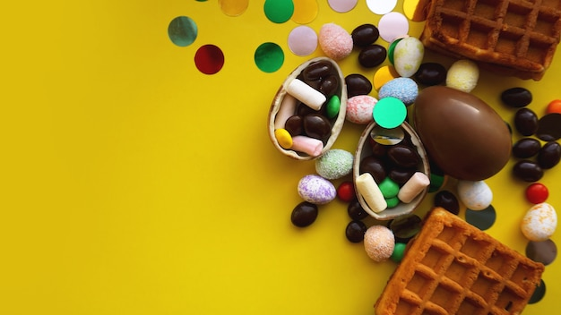 Heerlijke chocolade paaseieren, wafels, snoepjes op felgele achtergrond