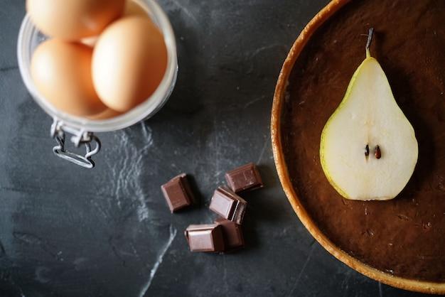 Heerlijke chocolade peren taart met ingrediënten op leisteen met tekst ruimte