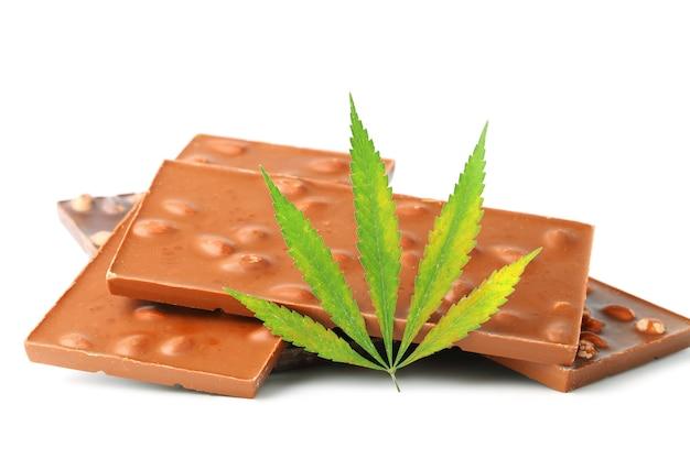 Heerlijke chocoladerepen met noten en groene hennepbladeren, chocolade met cbd-cannabis, geïsoleerd
