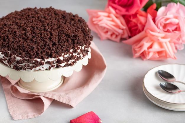Heerlijke chocoladetaart met room met een boeket rozen