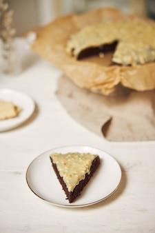 Heerlijke chocoladetaart met slagroom op een witte tafel gepresenteerd met esthetische details