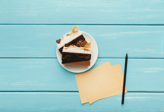 Heerlijke chocoladetaart op wit bord, pen en kleine papieren voor romantische berichten op turquoise houten tafel, bovenaanzicht, kopieerruimte