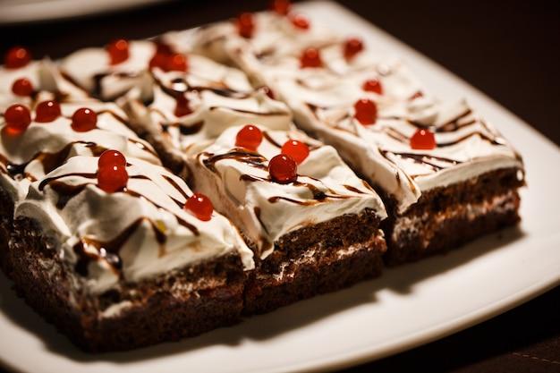 Heerlijke chocoladetaarten met botercrème, versierd met gelei van rode bessen op een witte plaat