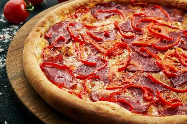 Heerlijke close-up op pittige gesneden pizza met ham, ui en chili. traditionele italiaanse keuken.