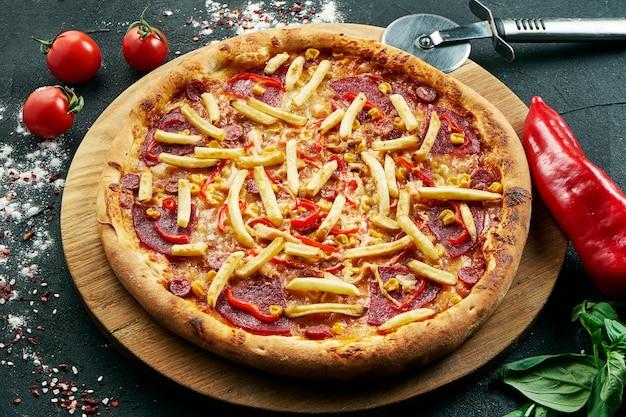 Heerlijke close-up op pittige pizza met ham, frietjes chili kaas. traditionele italiaanse keuken. pizza in samenstelling met ingrediënten op donkere tafel