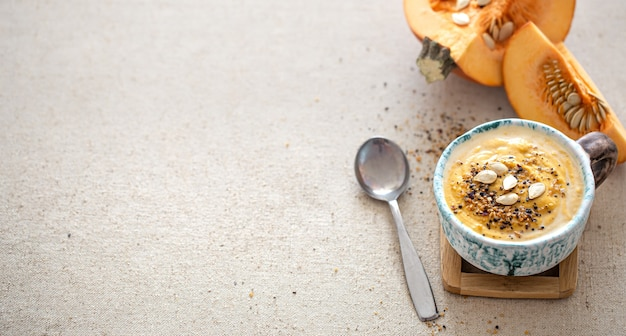 Heerlijke compositie met pompoensoep in een mooie keramische schotel bovenaanzicht. seizoensgebonden eten.