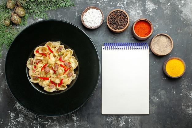 Heerlijke conchiglie met groenten en greens op een bord en mes en verschillende kruiden naast notitieboekje op grijze achtergrond