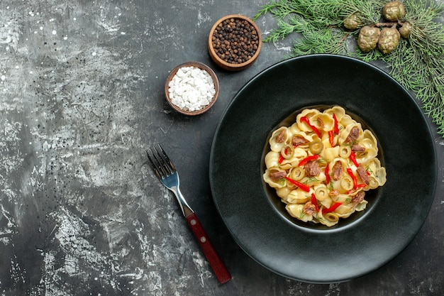 Heerlijke conchiglie met groenten en greens op een bord en mes en verschillende kruiden op grijze achtergrond