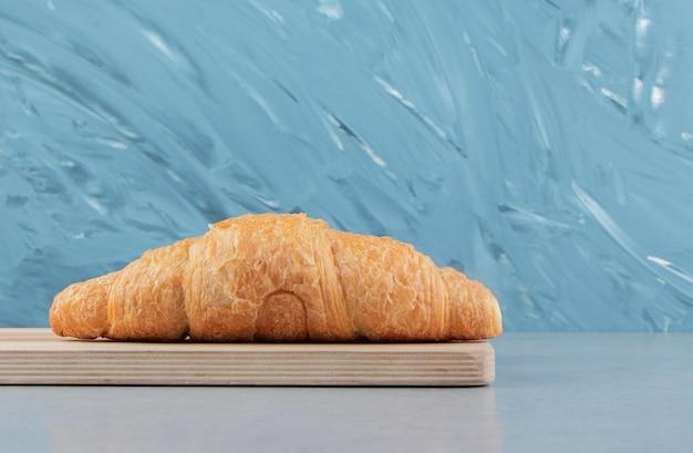 Heerlijke croissant op het bord, op de blauwe achtergrond. hoge kwaliteit foto