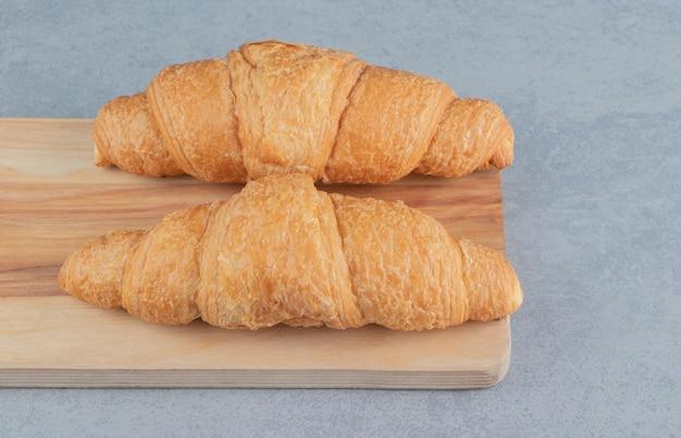 Heerlijke croissant op het bord, op de marmeren achtergrond. hoge kwaliteit bordfoto