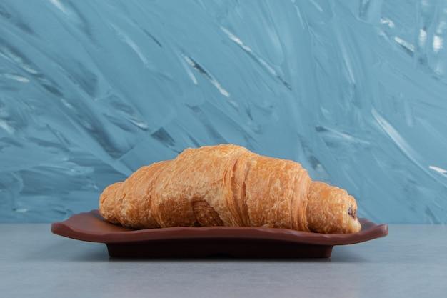 Heerlijke croissant op plaat, op de marmeren achtergrond. hoge kwaliteit foto