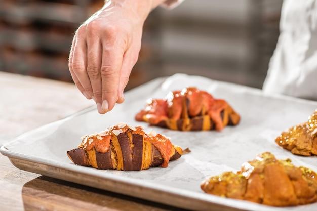 Heerlijke croissants. hand met gebakjekruimels boven croissant die het oppervlak versieren, gezicht is niet zichtbaar