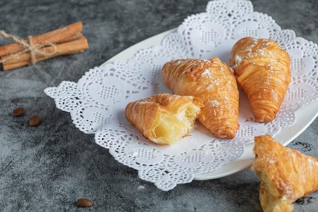 Heerlijke croissants met pijpjes kaneel op grijs.
