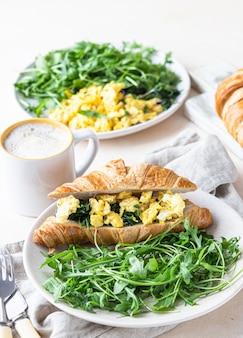 Heerlijke croissantsandwich met roerei spinazie eieren geserveerd met rucola op plaat en koffiekopje.
