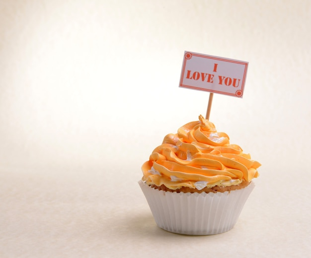 Heerlijke cupcake met inscriptie op tafel op beige