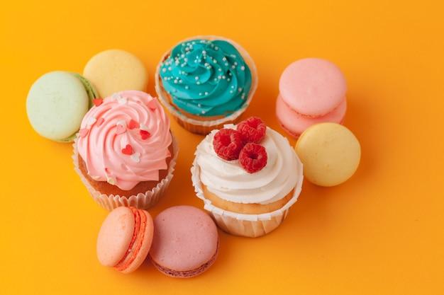 Heerlijke cupcakes met suikerglazuur op een gele achtergrond
