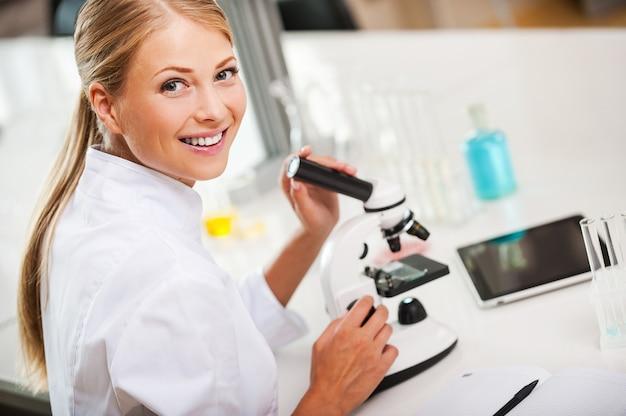 Heerlijke dag in het laboratorium. bovenaanzicht van lachende jonge vrouwelijke wetenschapper die de microscoop gebruikt en naar de camera kijkt terwijl hij in het laboratorium werkt