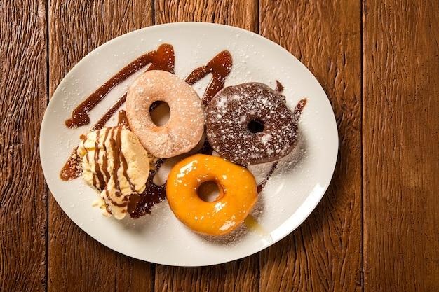 Heerlijke dessert donuts met ijs op een witte plaat met decoratie op een houten tafel