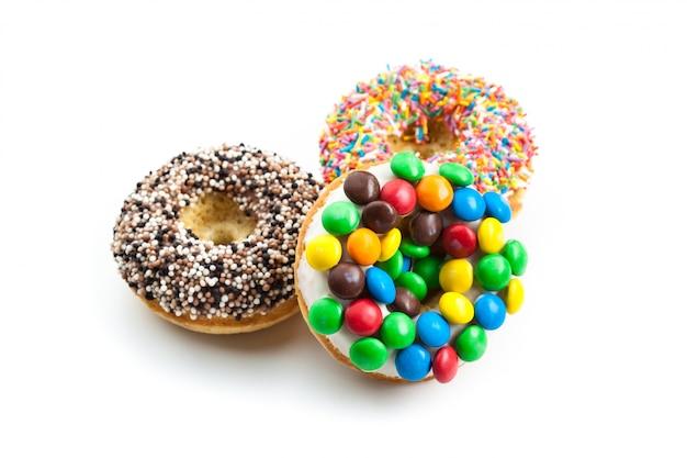 Heerlijke die donuts met suikerglazuur op wit wordt geïsoleerd