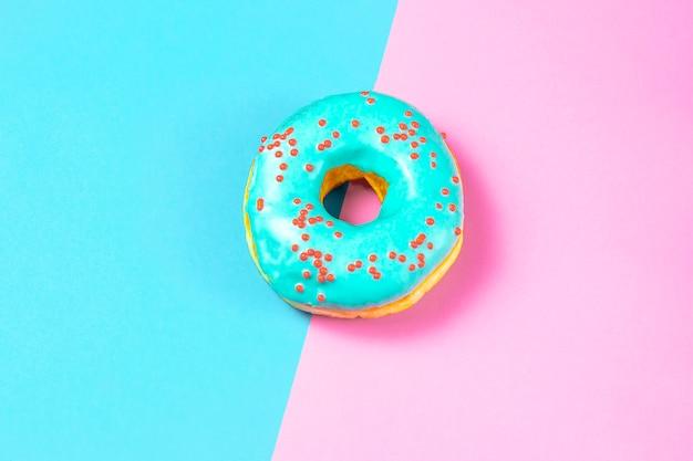 Heerlijke donut met blauw glazuur en strooi op een blauwe en roze tafel. zoet voedsel (dessert) concept. bovenaanzicht, platliggend