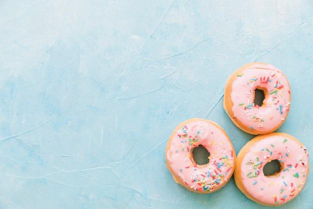 Heerlijke donuts met sprinkles op blauwe achtergrond