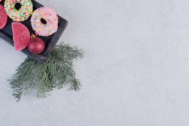 Heerlijke donuts met sproeiers en marmelade op zwarte plaat.