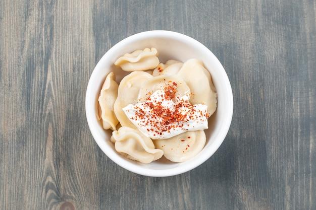 Heerlijke dumplings met rode peper in een witte kom