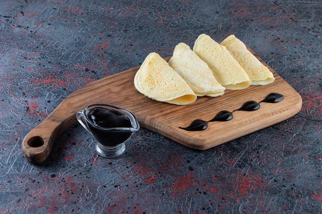 Heerlijke dunne pannenkoeken en chocoladesiroop op houten snijplank.