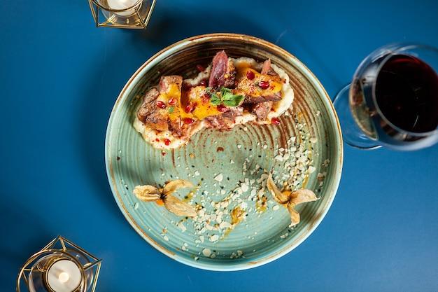 Heerlijke eendenborst met aardappelpuree en fruit op porselein, fijne gastronomie