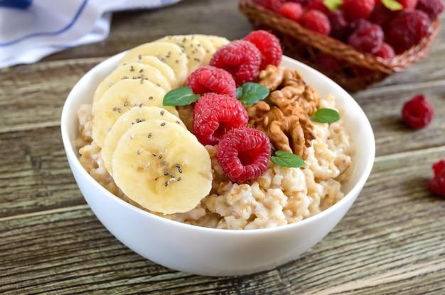 Heerlijke en gezonde havermout met banaan, frambozen, noten. gezond ontbijt. fitness eten. goede voeding.