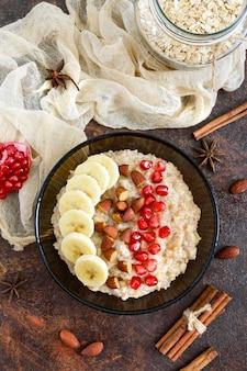 Heerlijke en gezonde havermout met banaan, granaatappelpitjes, amandel en kaneel. gezond ontbijt. fitness eten. goede voeding. plat leggen. bovenaanzicht.