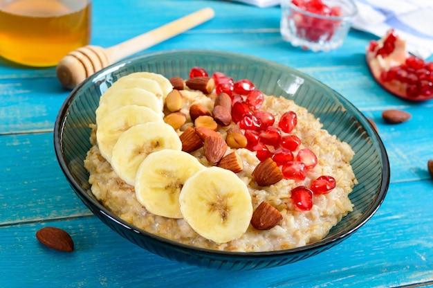 Heerlijke en gezonde havermout met banaan, granaatappelpitjes, amandel en kaneel. gezond ontbijt. fitness eten. goede voeding.