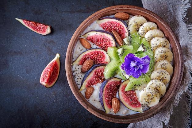 Heerlijke en gezonde havermout met vijgen, kiwi, banaan, amandel en chiazaden.