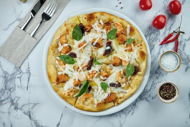 Heerlijke en knapperige italiaanse pizza met zeevruchten - zalm en tijgergarnalen, witte saus en gesmolten kaas in een bord op een marmeren oppervlak