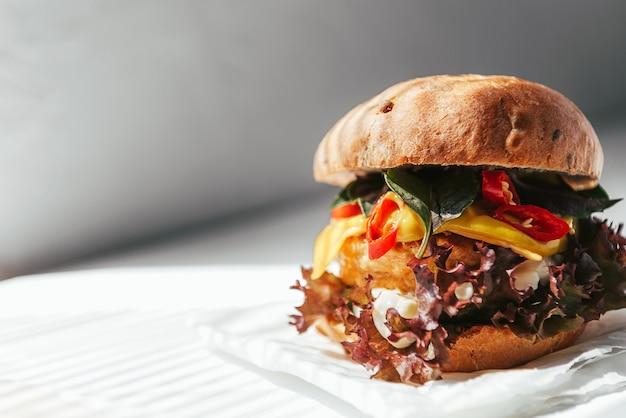 Heerlijke en smakelijke hamburger met kippenkotelet, basilicum en spaanse peperpeper op een witte houten achtergrond