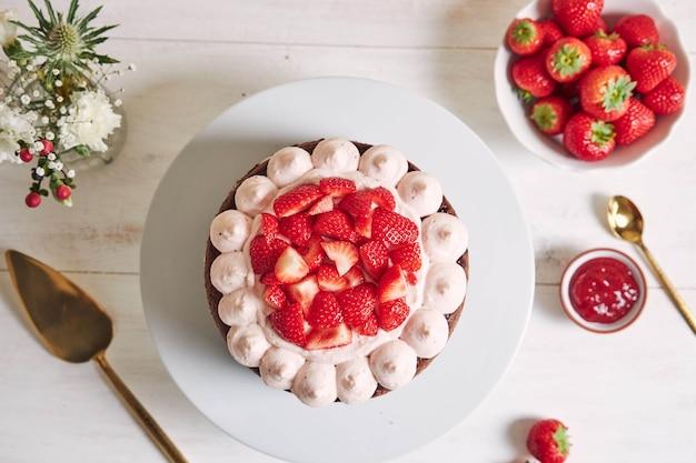 Heerlijke en zoete cake met aardbeien en baiser op een bord