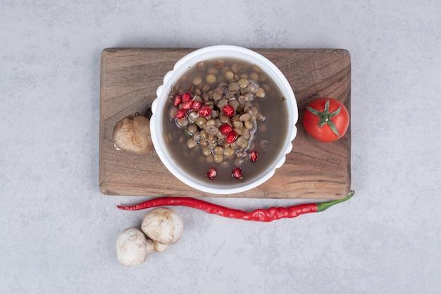 Heerlijke erwtensoep met champignons en tomaat op een houten bord.