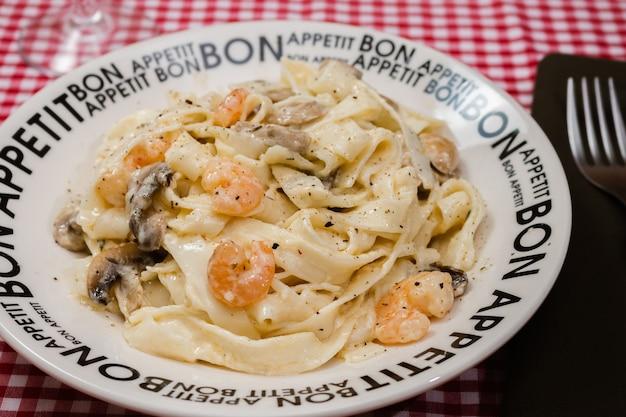 Heerlijke fettuccine met roomsaus van champignons en garnalen op een bord met daarop bon appetite met rood geruit tafelkleed. italiaanse keuken.