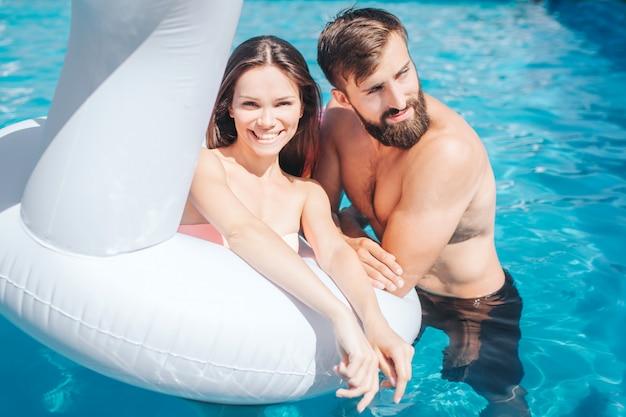 Heerlijke foto van het paar in het zwembad. het meisje zit luchtkussen en kijkt. ze lacht. guy leunt naar matras en kijkt naar rechts.