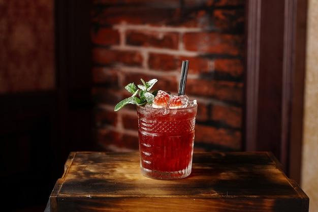 Heerlijke frambozen alcoholische cocktail met munt op een houten bord in de buurt van een bakstenen muur